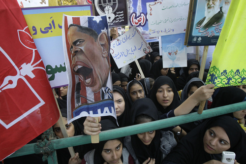 FILE-In this Friday, Nov. 2, 2012, file photo, Iranian girls, one of them holding up a caricature of President Barack Obama while others hold pro-government posters, attend an annual state-backed rally in front of the former U.S. Embassy in Tehran, Iran, commemorating 33rd anniversary of the embassy takeover by militant students. On Nov. 4, 1979, students who believed the embassy was a center of plots against Iran held 52 Americans hostages for 444 days, and the US severed formal diplomatic ties in response. In a sharp counterpoint to the Western outreach by President Hassan Rouhani's government, hard-line factions in Iran have amplified their bluster and backlash in messages that they cannot be ignored in any diplomatic moves with Washington either in the nuclear talks or beyond. (AP Photo/Vahid Salemi, File)