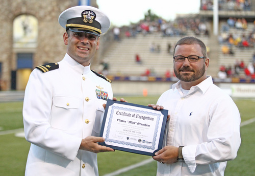 "In this Sept. 14, 2013 photo provided by the University of Toledo U.S. Army veteran Clinton ""Mick"" Grantham, right, receives the Hero of the Game award from U.S. Navy Lt. Haraz Ghanbari, the university's military liaison during a college football game in Toledo, Ohio. When Grantham, 43, enrolled at Toledo after back and neck problems forced him out of the Army, he plowed through his savings waiting for his disability benefits to kick in. Ghanbari arranged for the local American Legion to provide Grantham with a $500 grant, and pointed him to a job opening with the university's grounds crew. A veteran of Operation Enduring Freedom, Grantham in social work with an emphasis on veterans. (AP Photo/Daniel Miller, University of Toledo)"