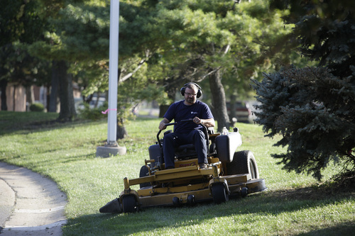 In this photo taken Tuesday, Oct. 1, 2013 photo Mick Grantham, 43, cuts the lawn at the University of Toledo's Medical Center in Toledo, Ohio. When Mick Grantham, 43, enrolled at Toledo after back and neck problems forced him out of the Army, he plowed through his savings waiting for his disability benefits to kick in. The universitiy's military liaison arranged for the local American Legion to provide Grantham with a $500 grant, and pointed him to a job opening with the university's grounds crew. (AP Photo/J.D. Pooley)