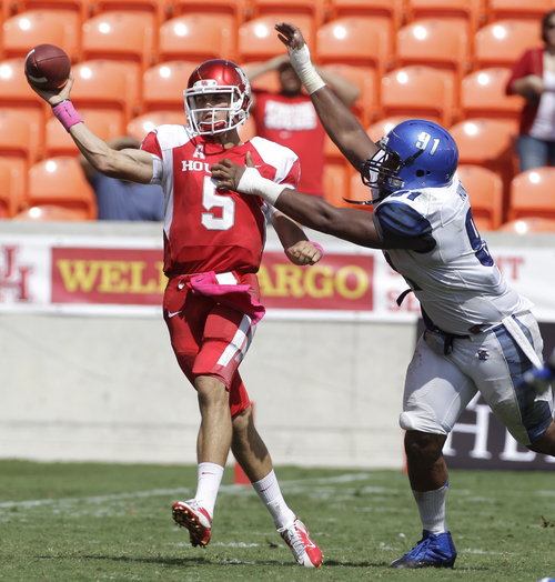 Houston quarterback John O'Korn is pressured by Memphis' Ricky Hunter during the third quarter of an NCAA college football game at BBVA Compass Stadium Saturday, Oct. 12, 2013, in Houston.  (AP Photo/Houston Chronicle, Melissa Phillip)