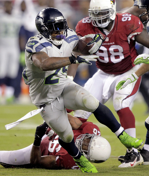 Seattle Seahawks running back Marshawn Lynch (24) breaks the tackle of Arizona Cardinals free safety Rashad Johnson (26) and defensive end Frostee Rucker during the second half of an NFL football game, Thursday, Oct. 17, 2013, in Glendale, Ariz. (AP Photo/Rick Scuteri)