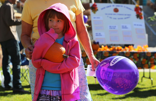 Francisco Kjolseth  |  The Salt Lake Tribune Olivia Jones, 5, patiently waits alongside her grandmother Marty Rawley for a chance to decorate a pumpkin at the Utah Foster Care Foundation's 12th Annual Pumpkin Festival at The Gateway Mall on Friday, Oct. 18, 2013.
