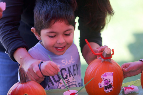 Francisco Kjolseth  |  The Salt Lake Tribune Diego Armas, 4, of West Valley gets excited about decorating his pumpkin with the help from his mother Marta during the Utah Foster Care Foundation's 12th Annual Pumpkin Festival at the Gateway Mall on Friday, Oct. 18, 2013.