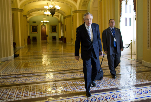 Senate Majority Leader Sen. Harry Reid, D-Nev., walks to his office after arriving on Capitol Hill on Wednesday, Oct. 16, 2013 in Washington. Aides to Senate Democrat Majority Leader Harry Reid and Republican Minority Leader Mitch McConnell said the leaders resumed talks Tuesday night and voiced optimism about striking an agreement Wednesday that could pass both houses of Congress and reach President Barack Obama's desk before Thursday, when the U.S. Treasury says it will begin running out of cash.   (AP Photo/ Evan Vucci)