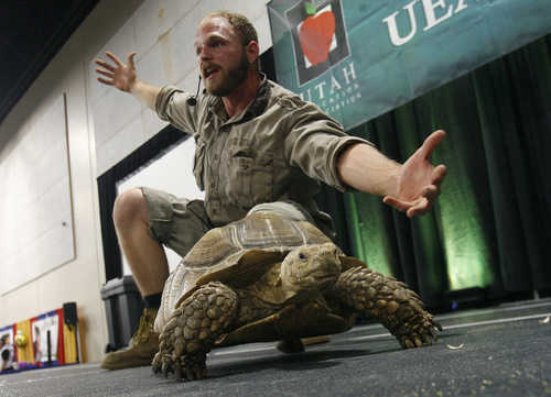 "Scott Sommerdorf   |  The Salt Lake Tribune Educating kids about animals, Animal Handler Austin Earley of ""Scales and Tails"" introduces ""Shelly"" the Sulcata Tortoise on Thursday at the two-day UEA convention at South Towne Exposition Center."