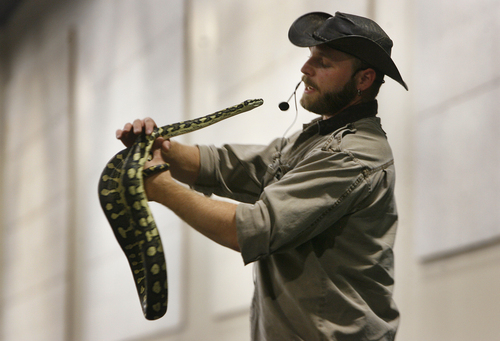 "Scott Sommerdorf   |  The Salt Lake Tribune Educating kids about animals, Animal Handler Austin Earley of ""Scales and Tails""  shows off ""Shaggy"" the Carpet Pythonon Thursday at the two-day UEA convention at South Towne Exposition Center."