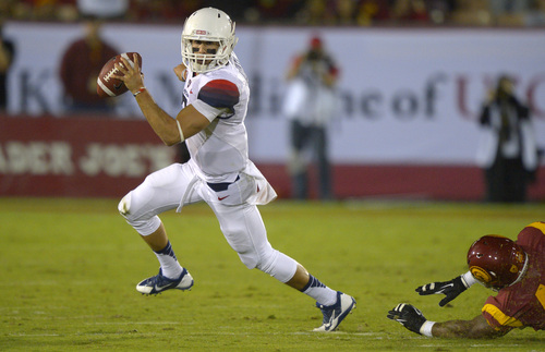 Arizona quarterback B.J. Denker, left, escapes a sack by Southern California linebacker Devon Kennard during the first half of an NCAA college football game, Thursday, Oct. 10, 2013, in Los Angeles. (AP Photo/Mark J. Terrill)