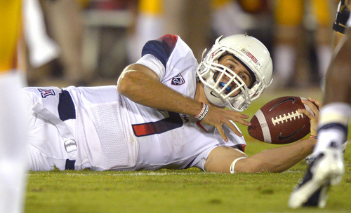 Arizona quarterback B.J. Denker lies on the ground after being tackled during the first half of an NCAA college football game against Southern California, Thursday, Oct. 10, 2013, in Los Angeles. (AP Photo/Mark J. Terrill)