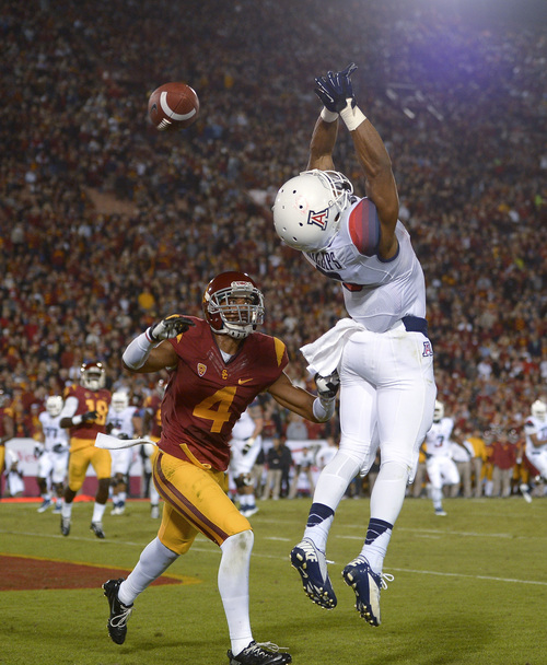 Arizona wide receiver Nate Phillips, right, has a pass go through his hands in the end zone as Southern California cornerback Torin defends during the first half of an NCAA college football game, Thursday, Oct. 10, 2013, in Los Angeles. (AP Photo/Mark J. Terrill)