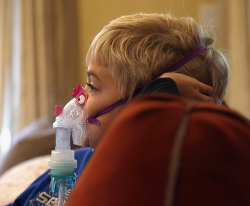 In this Tuesday, Oct. 15, 2013 photo, Carter Howard sits and watches a cartoon during his asthma treatment at his home in Northbrook, Ill. On the days when asthma gives Carter the most trouble, his mother is reminded how doctors at Rush University Medical Center had to stop submitting applications for research grants to study childhood asthma and other diseases and disorders due to the federal government shutdown. (AP Photo/Charles Rex Arbogast)