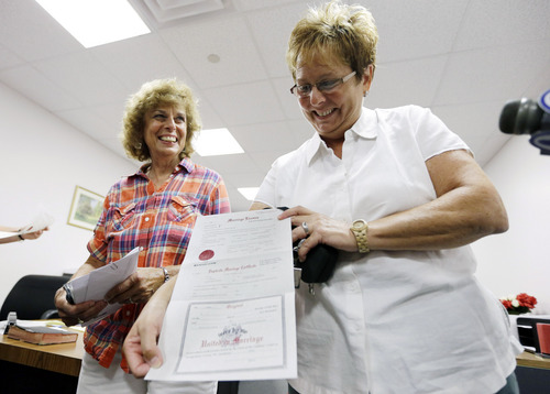 FILE - In this July 24, 2013 file photo, Ellen Toplin, right, and Charlene Kurland pose for photographs with their marriage license at a Montgomery County office despite a state law banning such unions, in Norristown, Pa.  Same-sex marriage advocates in Pennsylvania are pecking away at a 1996 ban by introducing bills in the Legislature, issuing marriage licenses, and taking the issue to court. (AP Photo/Matt Rourke, File)