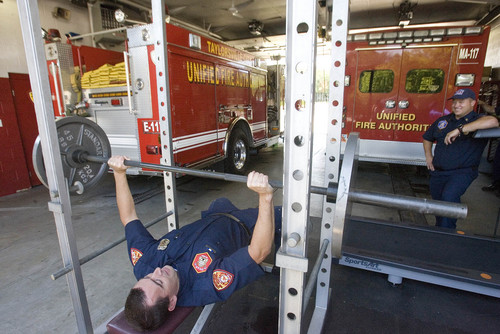 Paul Fraughton  |   The Salt Lake Tribune As Capt. Jeff Taylor looks on, Eric Benson  takes advantage of the exercise equipment that is wedged in next to the fire engines at Taylorsville Fire Station No. 117.                       Monday, September 9, 2013