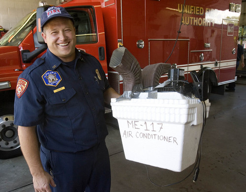 Paul Fraughton   |   The Salt Lake Tribune Capt. Jeff Taylor shows off an air conditioner cobbled together with duct tape -- a styrofoam cooler filled with ice, a 12-volt fan and some downspout elbows -- at Station No. 117.                       Monday, September 9, 2013