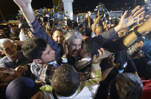 One of the nine Lebanese Shiite pilgrims who were kidnapped by a rebel faction in northern Syria in May 2012, hugs his relatives after his release, upon his arrival at Rafik Hariri international airport, in Beirut, Lebanon, Saturday, Oct. 19, 2013. Two Turkish pilots held hostage in Lebanon and nine Lebanese pilgrims abducted in Syria returned home Saturday night, part of an ambitious three-way deal cutting across the Syrian civil war. (AP Photo/Hussein Malla)