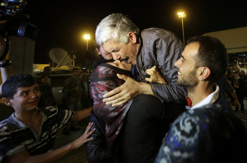 One of nine released Lebanese Shiite pilgrims who were kidnapped by a rebel faction in northern Syria in May 2012, center, kisses his wife upon his arrival at Rafik Hariri international airport, in Beirut, Lebanon, Saturday, Oct. 19, 2013. Two Turkish pilots held hostage in Lebanon and nine Lebanese pilgrims abducted in Syria returned home Saturday night, part of an ambitious three-way deal cutting across the Syrian civil war.(AP Photo/Hussein Malla)
