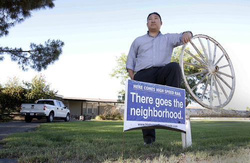 In this photo taken Tuesday, July 16, 2013, high-speed rail opponent Aaron Fukuda poses in front of his Hanford, Calif.,  home that lies directly in one of the planned train routes.  Fukuda is one of many land owners in the Central Valley who have sued to try to stop the $68 billion project.  The state is buying up hundreds of properties to start construction of the first 30 mile segment of the rail line. Voters approved plans to build the bullet train five years ago, but public opinion about the project has since soured, and many now oppose it. (AP Photo/Rich Pedroncelli)