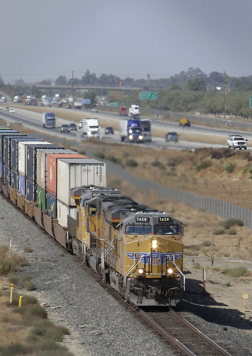 In this photo taken Thursday, Oct. 10, 2013, a freight train travels south alongside Highway 99 near Livingston, Calif. Construction of the nation's first high-speed rail system is slated to begin in Fresno  promising to create construction jobs and link the Central Valley to the rest of California.  Many Californians have soured on the $68 billion plan in the five years since voters approved $10 billion in bonds for it.(AP Photo/Rich Pedroncelli)