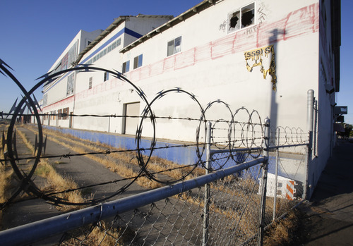In this photo taken Wednesday, July 17, 2013,  an abandoned building sits on the route for California's planned high-speed rail line in Fresno, Calif.   Work is set to start on the first 30 mile segment of track in this city of 500,000 people with soaring unemployment and a withering downtown core.  The rail line was sold to voters five years ago as a way to create jobs, cut pollution and ease gridlock, but many residents have since soured on the $68 billion plan. (AP Photo/Rich Pedroncelli)