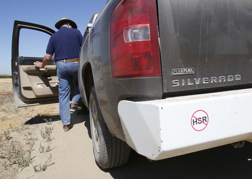 "In this photo taken Tuesday, July 16, 2013,   farmer Kole Upton climbs into his pickup  which bears  a sticker showing his opposition to the proposed high-speed rail system, at his ranch in Chowchilla, Calif.   Upton  is among many farmers in the Central Valley who say plans to build the $68 billion bullet train have led to years of uncertainty and financial burden. Upton says his family has put plans on hold to replace almond trees on the 1,400 acre farm as they await word on the final route.  ""They put a cloud on your land,"" Upton says.(AP Photo/Rich Pedroncelli)"