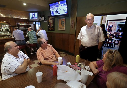 "In this photo taken Wednesday, July 17, 2013, Gary Lanfranco, owner of the Cosmopolitan Cafe, standing, talks with lunchtime customers at the downtown  Fresno, Calif. eatery that sits in the path of the high-speed rail line.  Lanfranco's  restaurant is one of hundreds of properties the state needs to buy  or seize in the Central Valley to start construction of the first 30 mile segment of the rail line. ""I've put the last 45 years of my life"" into the restaurant, says Lanfranco, who was dissatisfied with the initial offer he received from the California High- Speed Rail Authority. (AP Photo/Rich Pedroncelli)"