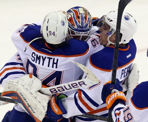 Edmonton Oliers goaltender Devan Dubnyk (40) celebrates with teammates Ryan Smith and David Perron (77) after they defeated the Ottawa Senators 3-1 in an NHL hockey in Ottawa, Saturday, Oct. 19, 2013. (AP Photo/The Canadian Press, Fred Chartrand)