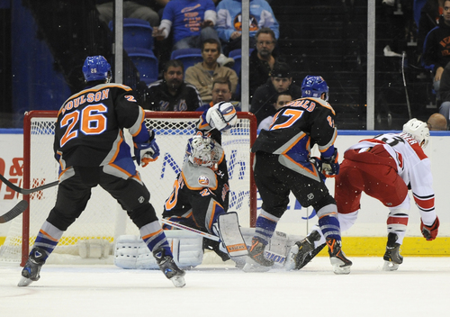 Carolina Hurricanes' Jeff Skinner (53) shoots the puck past New York Islanders goalie Evgeni Nabokov (20) as Matt Moulson (26) and Andrew MacDonald (47) watch from behind in the second period of an NHL hockey game Saturday, Oct. 19, 2013, in Uniondale, N.Y. (AP Photo/Kathy Kmonicek)