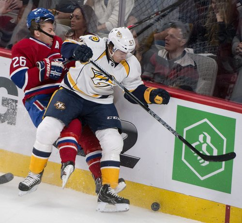 Montreal Canadiens' Josh Gorges takes a hard hit on the boards from Nashville Predators' Gabriel Bourque during the first period of an NHL hockey game, Saturday, Oct. 19, 2013 in Montreal. (AP Photo/The Canadian Press, Peter McCabe)