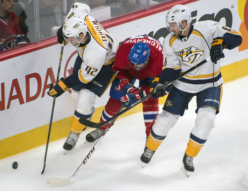 Montreal Canadiens' Alex Galchenyuk, center, battles for the buck with Nashville Predators' Mattias Ekholm (42), and Kevin Klein during the third period of an NHL hockey game, Saturday, Oct. 19, 2013 in Montreal. (AP Photo/The Canadian Press, Peter McCabe)