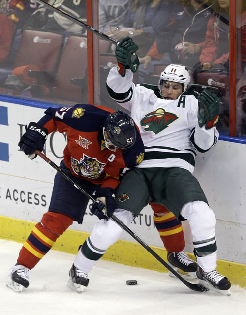 Florida Panthers center Marcel Goc (57) checks Minnesota Wild left wing Zach Parise, righ, in the third period of an NHL hockey game, Saturday, Oct. 19, 2013, in Sunrise, Fla. (AP Photo/Alan Diaz)