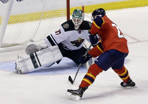 Florida Panthers center Brad Boyes (24) dives to score a goal against Minnesota Wild goalie Josh Harding (37) in a shoot-out during an NHL hockey game, Saturday, Oct. 19, 2013, in Sunrise, Fla. The Panthers won 2-1. (AP Photo/Alan Diaz)