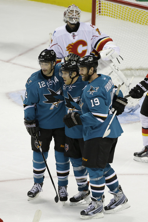 San Jose Sharks center Joe Pavelski is greeted by teammates Patrick Marleau (12) and Joe Thornton (19) after scoring the Sharks' fifth goal during the third period of an NHL hockey game Saturday, Oct. 19, 2013, in San Jose, Calif. Looking on in the background is Calgary Flames goalie Karri Ramo. San Jose won the game 6-3. (AP Photo/Eric Risberg)