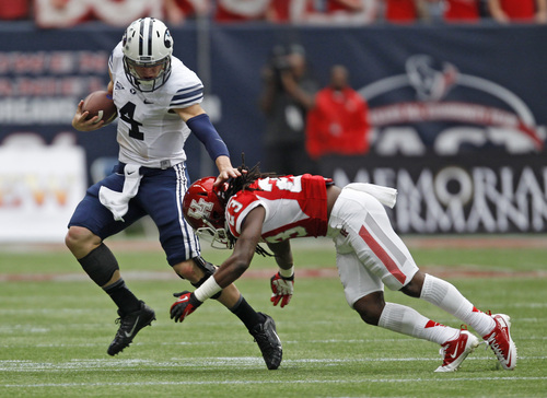 BYU's Taysom Hill (4) avoids the tackle of Houston's Trevon Stewart (23) during the first half of an NCAA college football game, Saturday, Oct. 19, 2013 in Houston. (AP Photo/Eric Christian Smith)