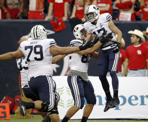 BYU's Skyler Ridley (17) celebrates his game-winning touchdown reception with Kaneakua Friel (82) and Makaaki Vaitai (79) during the second half of an NCAA college football game, Saturday, Oct. 19, 2013 in Houston. BYU defeated Houston, 47-46. (AP Photo/Eric Christian Smith)