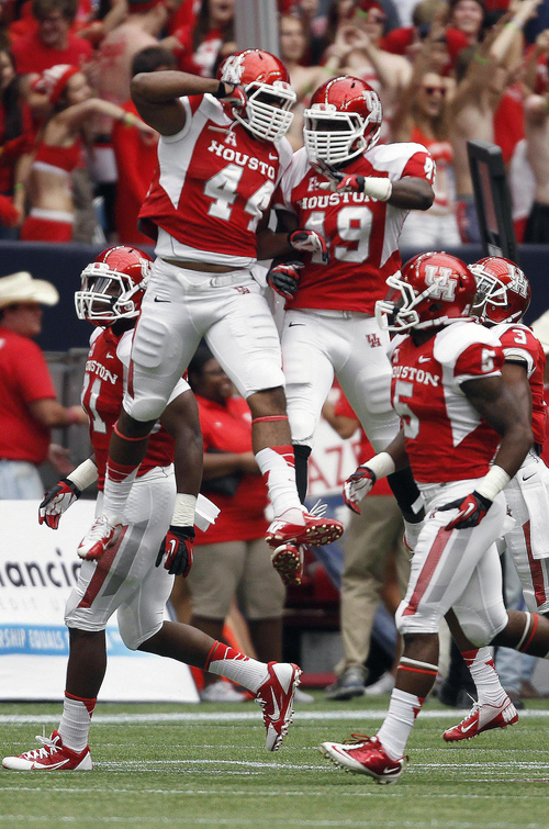 Houston's Derrick Matthews (49) celebrates his interception return for a touchdown with Elandon Roberts during the first half of an NCAA college football game against BYU, Saturday, Oct. 19, 2013 in Houston. (AP Photo/Eric Christian Smith)