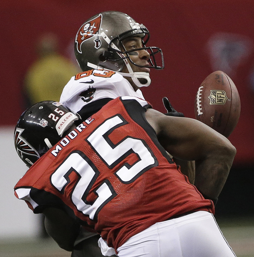 Tampa Bay Buccaneers wide receiver Vincent Jackson (83) misses the catch against Atlanta Falcons strong safety William Moore (25) during the second half of an NFL football game, Sunday, Oct. 20, 2013, in Atlanta. (AP Photo/John Bazemore)