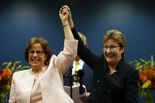Beth Asaro, left, and Joanne Schailey celebrate after exchangeing vows to become the first same-sex couple married in Lambertville, N.J.  history at 12:01 a.m. Monday, Oct. 21, 2013 in Lambertville, N.J. Asaro and Schailey hold the distinction of being the first couple to enter into a civil union in the state, when that law took effect in 2007. (AP Photo/Rich Schultz)