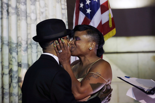 Lydia Torres, left, 44, and Jenelle Torres, 42, right, kiss after Newark Mayor and Senator-elect Cory Booker, officiated their wedding ceremony  at Newark City Hall just after midnight Monday, Oct. 21, 2013.  (AP Photo/Mel Evans)