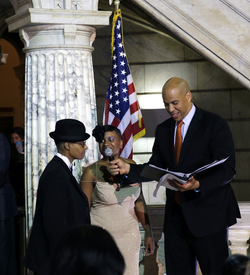 Newark Mayor and Senator-elect Cory Booker, right, officiates the ceremony for the  same-sex marriage of Lydia Torres, left, 44, and Jenelle Torres, 42, center, at Newark City hall just after midnight Monday, Oct. 21, 2013.  (AP Photo/Mel Evans)
