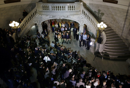 A large crowd looks on as Newark Mayor and Senator-elect Cory Booker, right, officiates the ceremony for the  same-sex marriage of Anthony Arenas, center,36, and Alexander Padilla, 37, at Newark City hall just after midnight Monday, Oct. 21, 2013.  (AP Photo/Mel Evans)