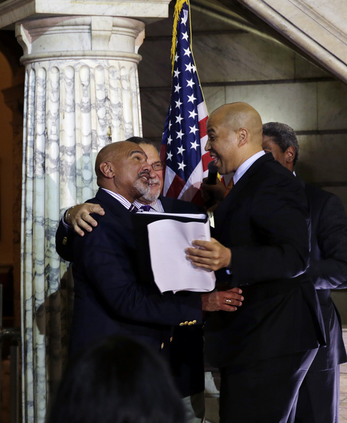 Newark Mayor and Senator-elect Cory Booker, right, shares a hug after officiating the first same-sex marriage in Newark for Joesph Panessidi, center, 65, and Orville Bell, left, 65, in Newark City hall just after midnight Monday, Oct. 21, 2013.  (AP Photo/Mel Evans)