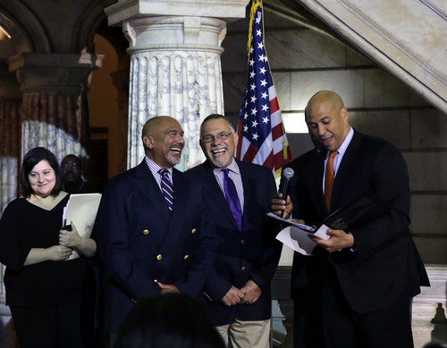 Newark Mayor and Senator-elect Cory Booker, left, shares a laugh as he officiates the first same-sex marriage for Joesph Panessidi, center right, 65, and Orville Bell, 65, in Newark City hall just after midnight Monday, Oct. 21, 2013.  (AP Photo/Mel Evans)