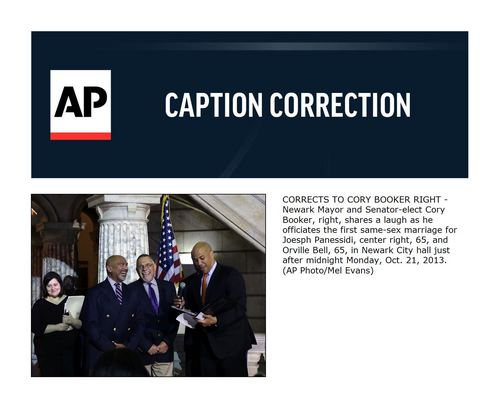 CORRECTS TO CORY BOOKER RIGHT -Newark Mayor and Senator-elect Cory Booker, right, shares a laugh as he officiates the first same-sex marriage for Joesph Panessidi, center right, 65, and Orville Bell, 65, in Newark City hall just after midnight Monday, Oct. 21, 2013.  (AP Photo/Mel Evans)