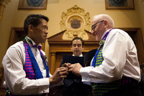 David Gibson, right, and Richard Kiamco of Jersey City make history as they become the first official same-sex couple to be married in Jersey City in a ceremony officiated by Mayor Steve Fulop at 12:01 a.m. Monday, Oct. 21, 2013, at City Hall. Seven other gay couples also participated in the ceremony. (AP Photo/The Jersey Journal, Reena Rose Sibayan)