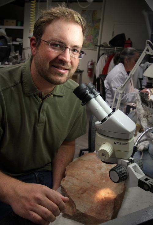 Rick Egan  | The Salt Lake Tribune   University of Utah paleontologist Randall Irmis examines a Triassic fossil of a fish he found in southeastern Utah at the Utah Museum of Natural History