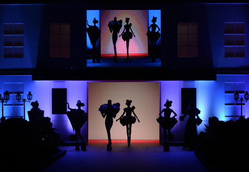 Models are silhouetted as they wear creations by Chinese fashion designer Guo Pei during the Fide Fashion Week 2013 Asian Couture show in Singapore, Wednesday, Oct. 16, 2013. (AP Photo/Wong Maye-E)