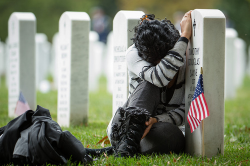 Thania Sayne of Effingham, Ill., collapses against the grave of her husband, Army Sgt. Timothy D. Sayne, during the playing of taps at a nearby burial service at Arlington National Cemetery, in Arlington, Va., Wednesday, Oct. 16, 2013, a day before what would have been their third wedding anniversary.  Sayne, was 4 months pregnant with their second son, Douglas, when her husband was killed on Sept. 18, 2011, in the Kandahar province of Afghanistan.  (AP Photo/Manuel Balce Ceneta)