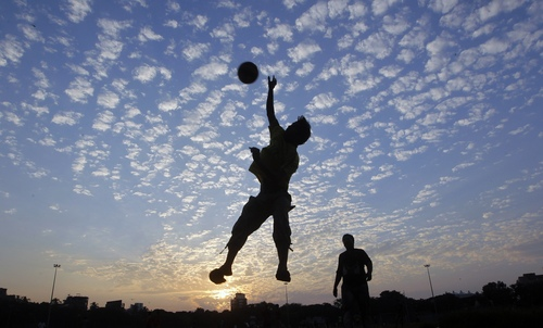 An Indian boy jumps to catch a ball at Shivaji Park in Mumbai, India, Friday, Oct.18, 2013. Shivaji Park is the largest park in Mumbai and has been a training ground for several Indian cricketers, including Sachin Tendulkar. (AP Photo/Rajanish Kakade)