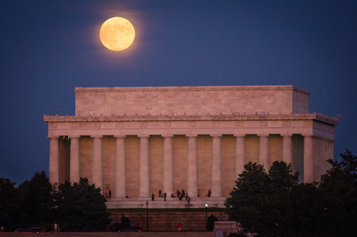 People watch the sunset from the Lincoln Memorial in Washington as a full moon raises in the background, Friday, Oct. 18, 2013. (AP Photo/J. David Ake)