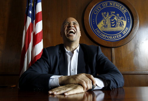 In this Aug. 10, 2011 photo, Newark Mayor Cory Booker laughs while posing for The Associated Press in his office in Newark, N.J. The Newark that Booker is leaving behind as the state's newly-elected U.S. senator is far more nuanced and complicated than could be captured in the boosterish campaign stump speeches or television sound bites for which the mayor is known. Newark still bears the scars of the 1967 riots that cleaved it. Poverty and crime are endemic. Lately, however, parts of the city have doggedly improved. (AP Photo/Julio Cortez)