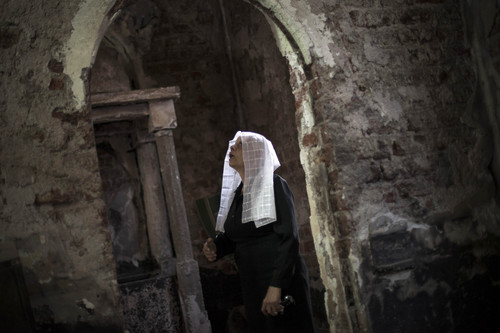 In this Thursday, Oct. 2, 2013 photo, an Egyptian Coptic woman prays at a church burnt by radical Islamists on Aug. 14 near Assiut, 320 kilometers (200 miles) south of Cairo. In a show of resilience, some have held masses and weddings in churches that have been left blackened shells without doors or windows, with only a makeshift altar. Still, priests say, some regular worshippers have stayed away, too hurt to return and see the condition of the churches where they lived out milestones like weddings, baptisms and funerals.(AP Photo/Manu Brabo)